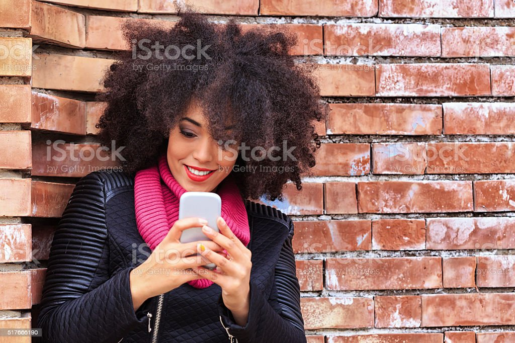 Beautiful young woman leaning against a brick wall typing message stock photo