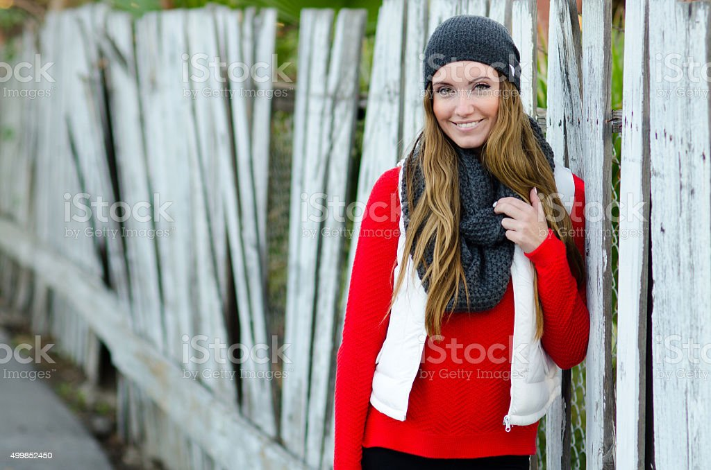Beautiful young woman leaning on fence in winter wardrobe stock photo