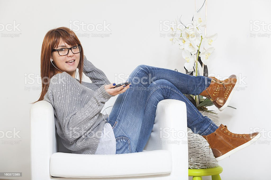 Beautiful Young Woman Listening Music on the Sofa royalty-free stock photo