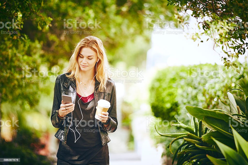 Beautiful young woman listening music while holding disposable c stock photo