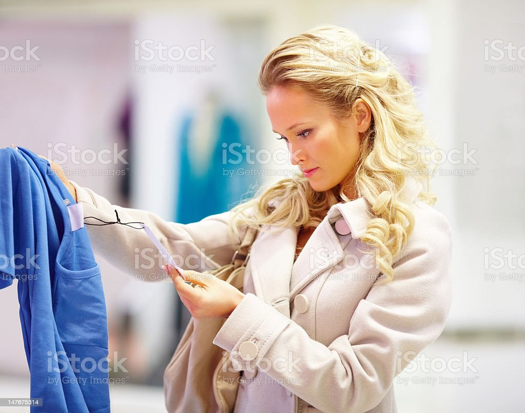 Beautiful young woman looking at price tag of cloth royalty-free stock photo