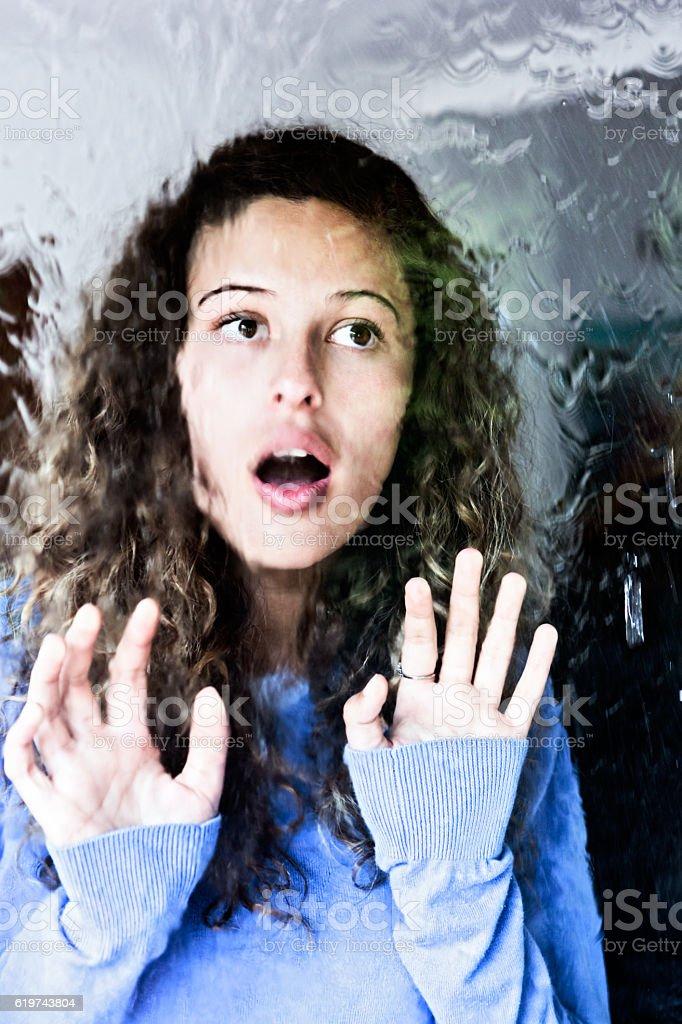 Beautiful young woman looks through rain-streaked window, surprised stock photo
