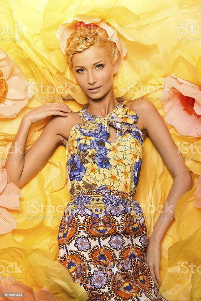 Beautiful young woman lying among big yellow flowers royalty-free stock photo