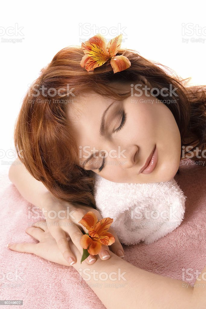 Beautiful young woman lying down for massage  with orchids. royalty-free stock photo
