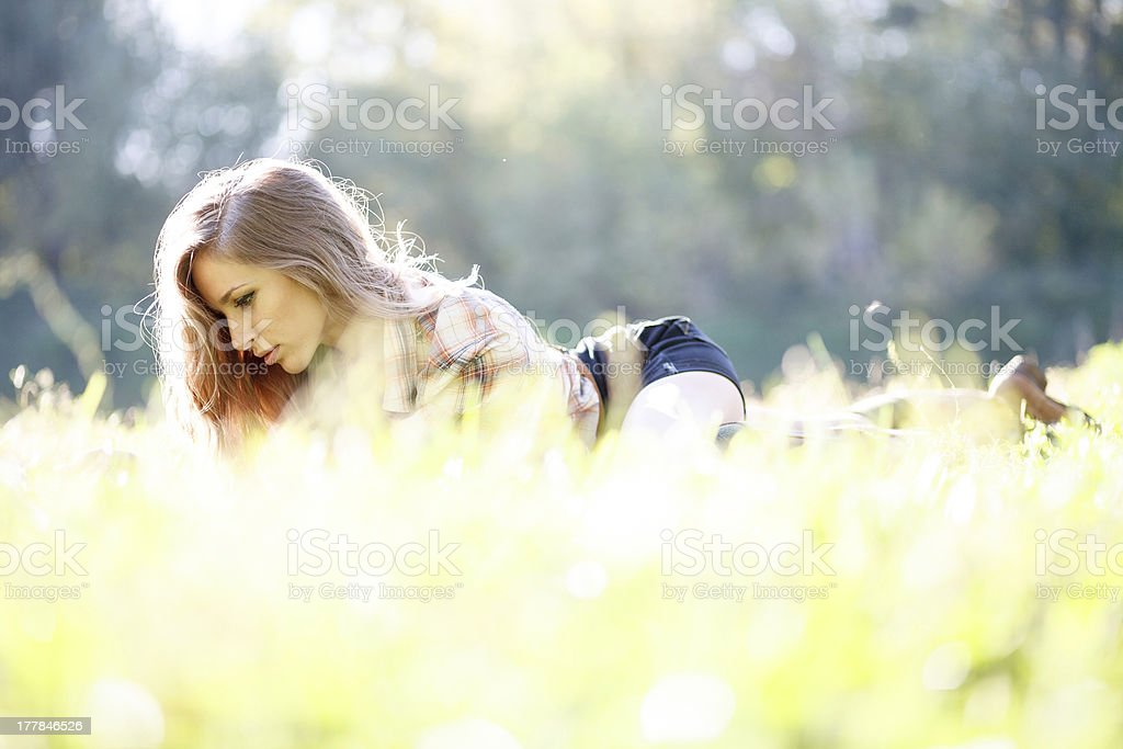 Beautiful Young Woman lying down on grass reading royalty-free stock photo