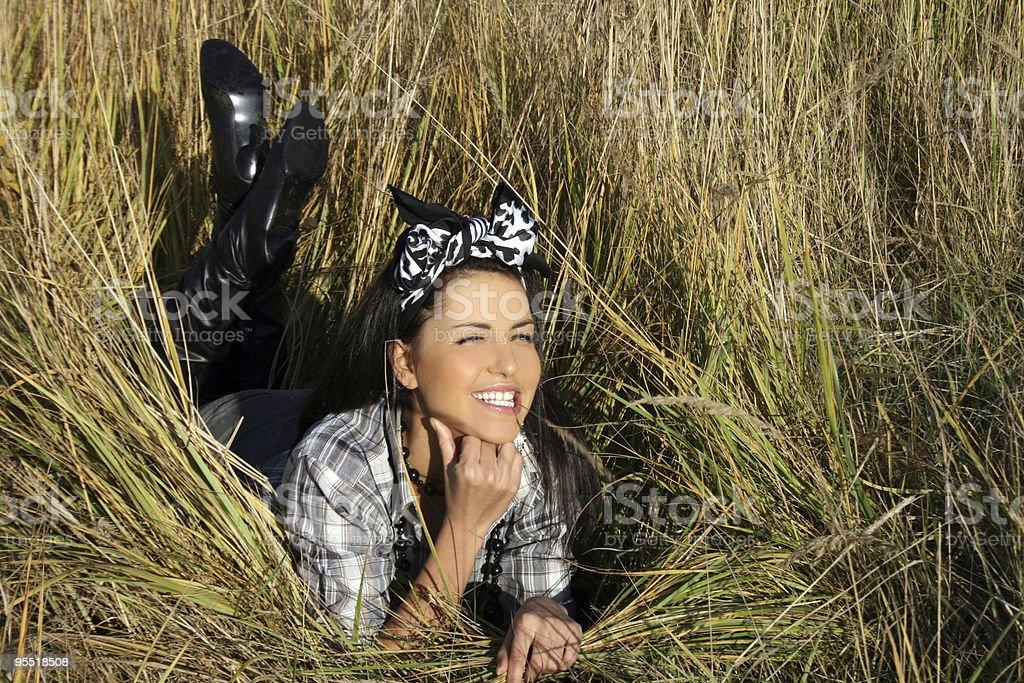 Beautiful young woman lying on field royalty-free stock photo