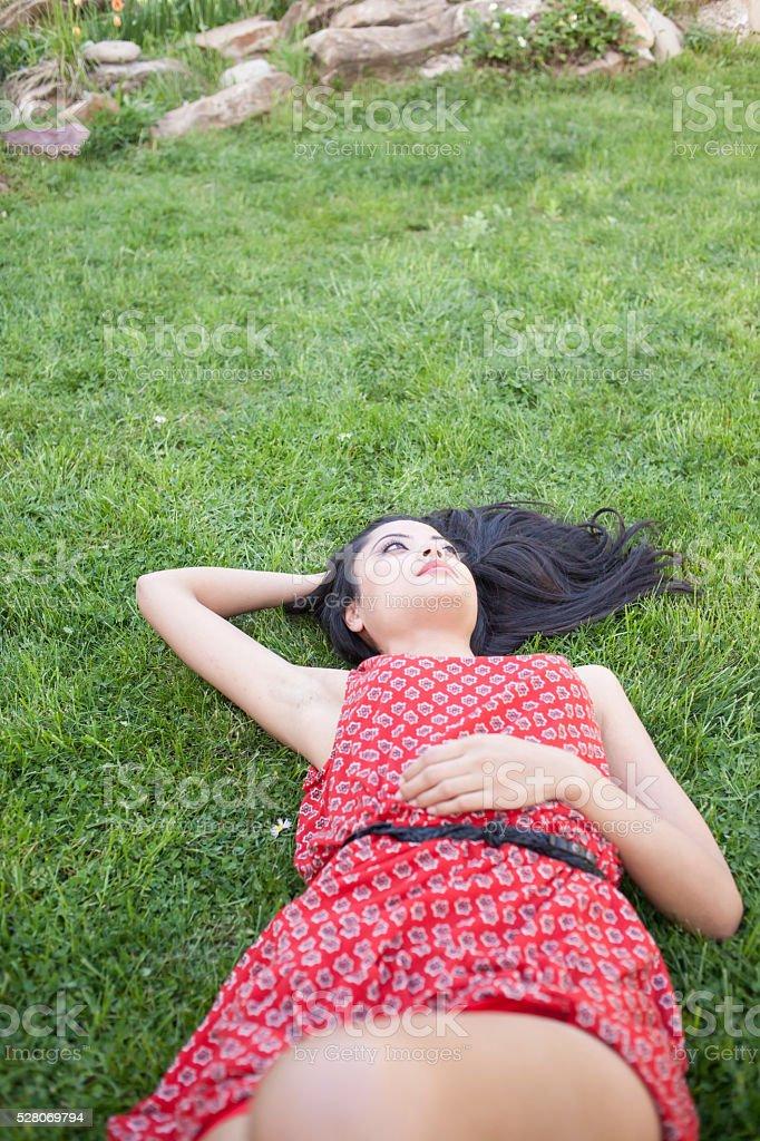 Beautiful young woman lying on grassland stock photo