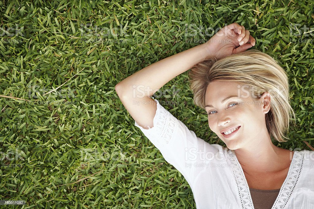 Beautiful, young woman lying on green grass royalty-free stock photo