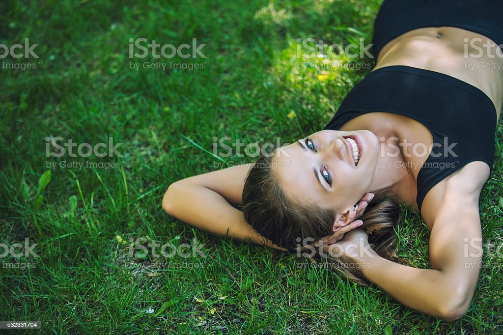 Beautiful young woman lying on the grass stock photo