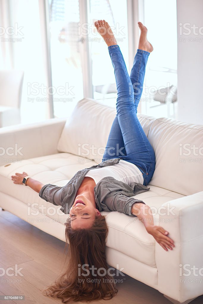 Beautiful young woman lying upside down on couch stock photo