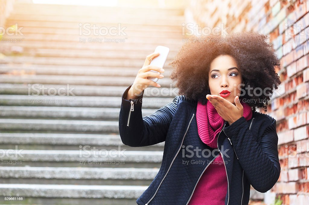 Beautiful young woman making selfie and sending air kiss stock photo