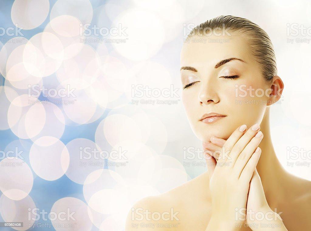 Beautiful young woman massaging her face stock photo