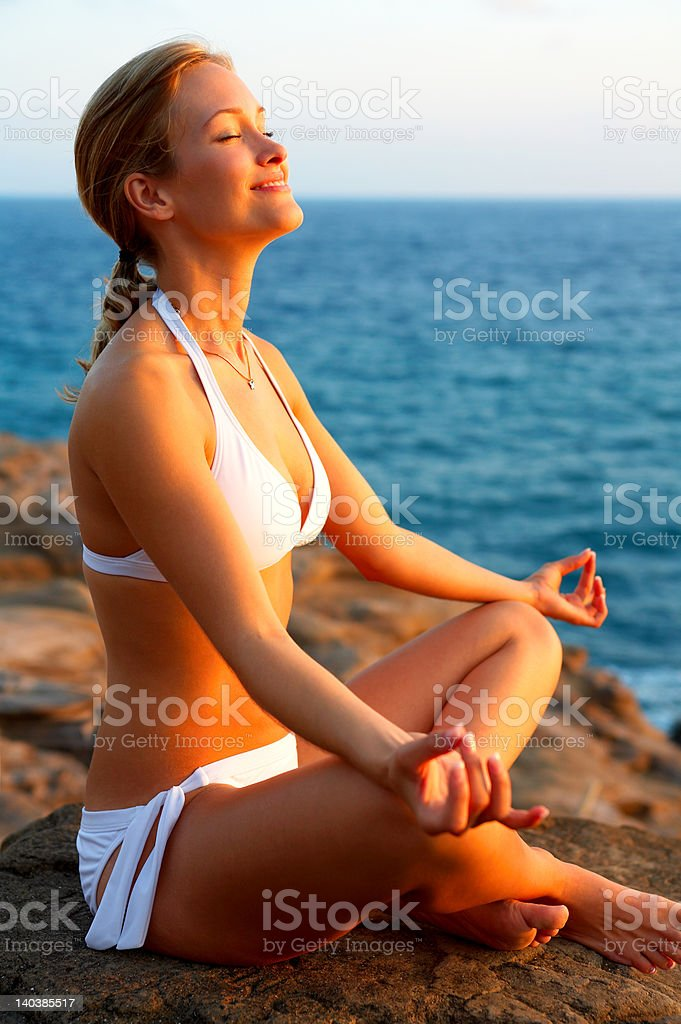 Beautiful young woman meditating by the sea royalty-free stock photo