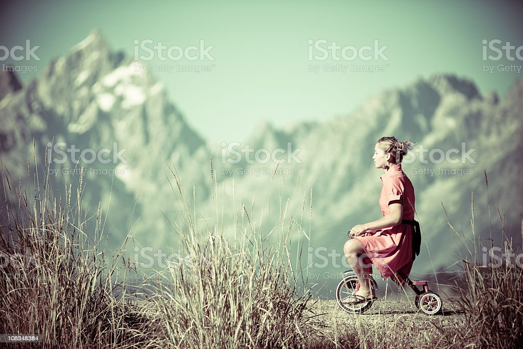 Beautiful young woman on a little tricycle royalty-free stock photo