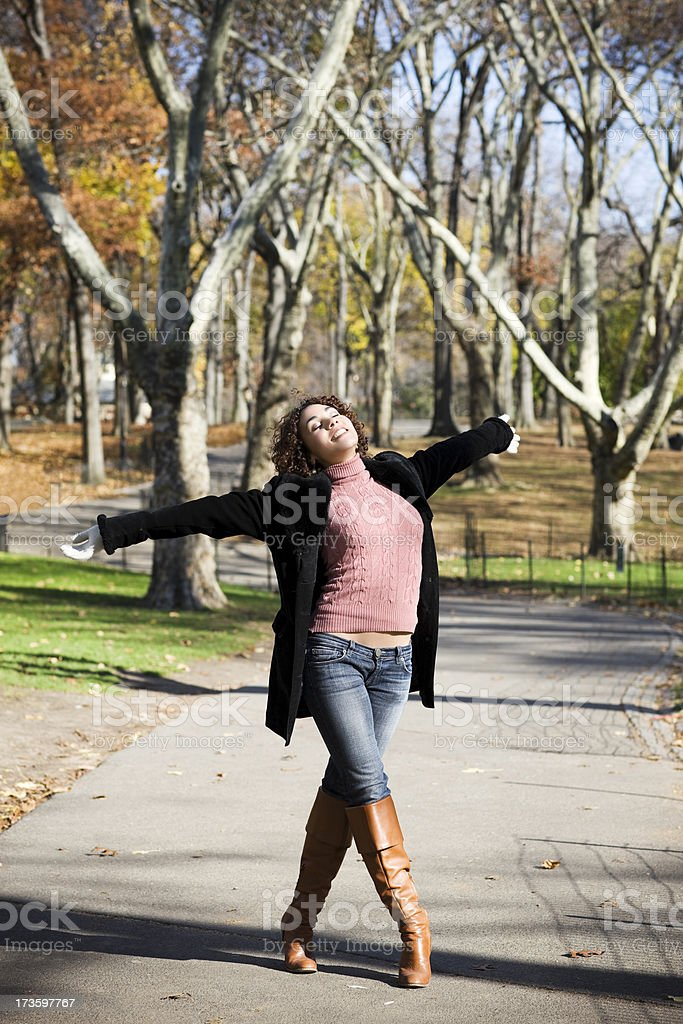 Beautiful Young Woman on Fall Sidewalk, Arms Outstretched royalty-free stock photo