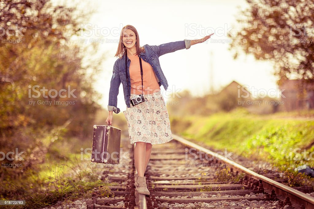 Beautiful young woman on railroad tracks stock photo