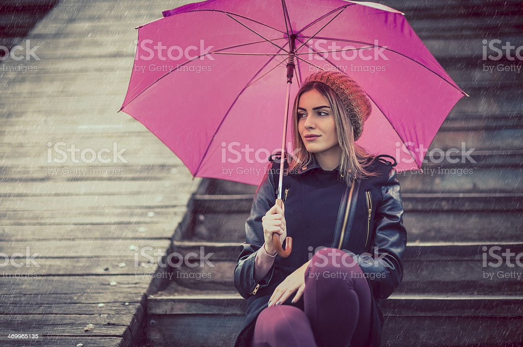 Beautiful young woman on rainy day outdoors royalty-free stock photo