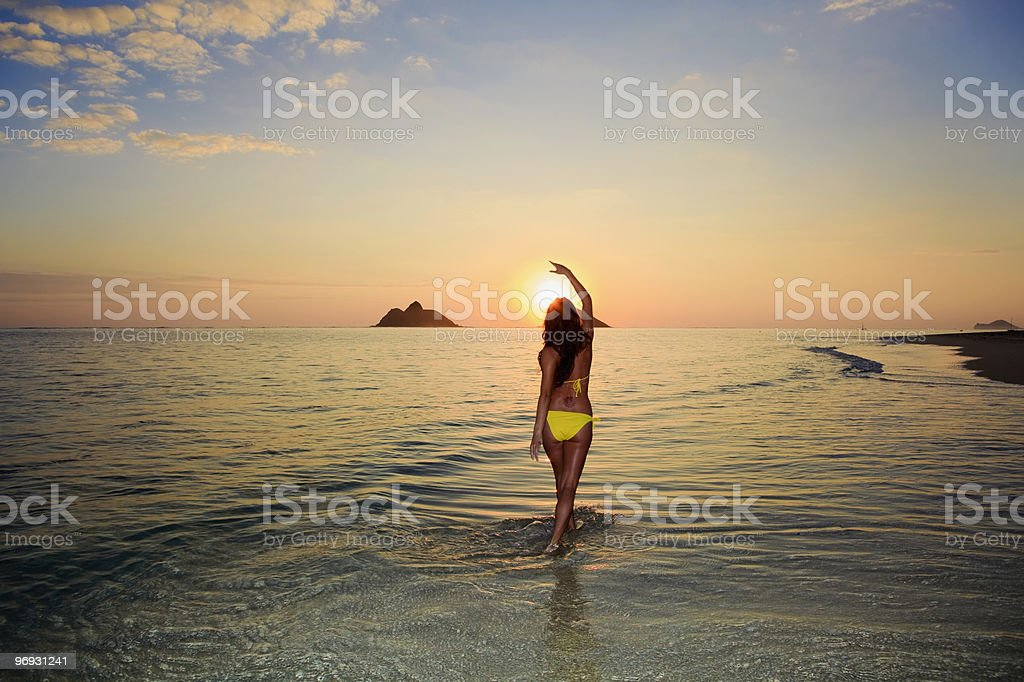 beautiful young woman on the beach at sunrise stock photo