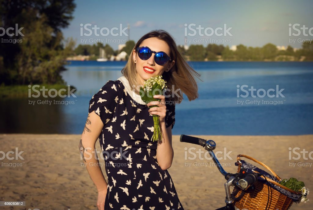 Beautiful young woman on the beach with bicycle and flowers stock photo
