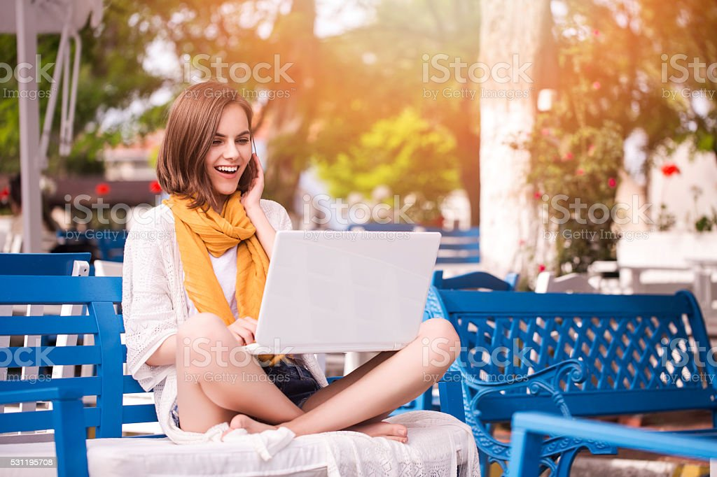 Beautiful young woman outdoors with a laptop stock photo