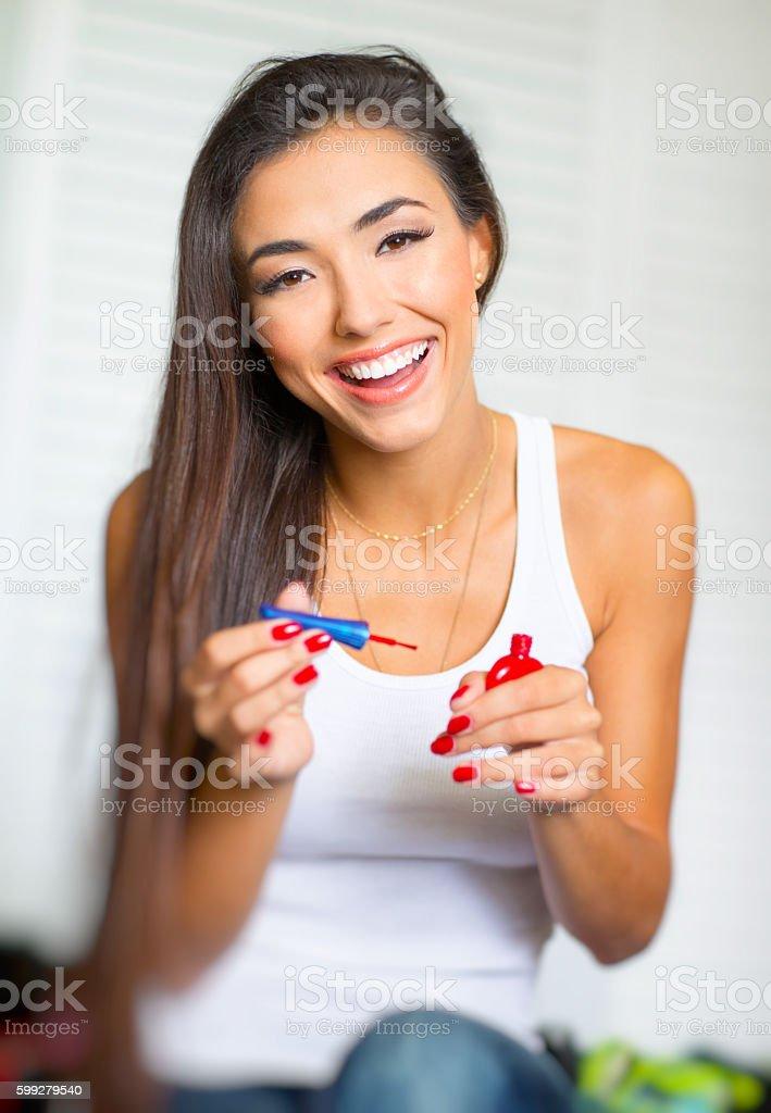 beautiful young woman painting fingernails stock photo