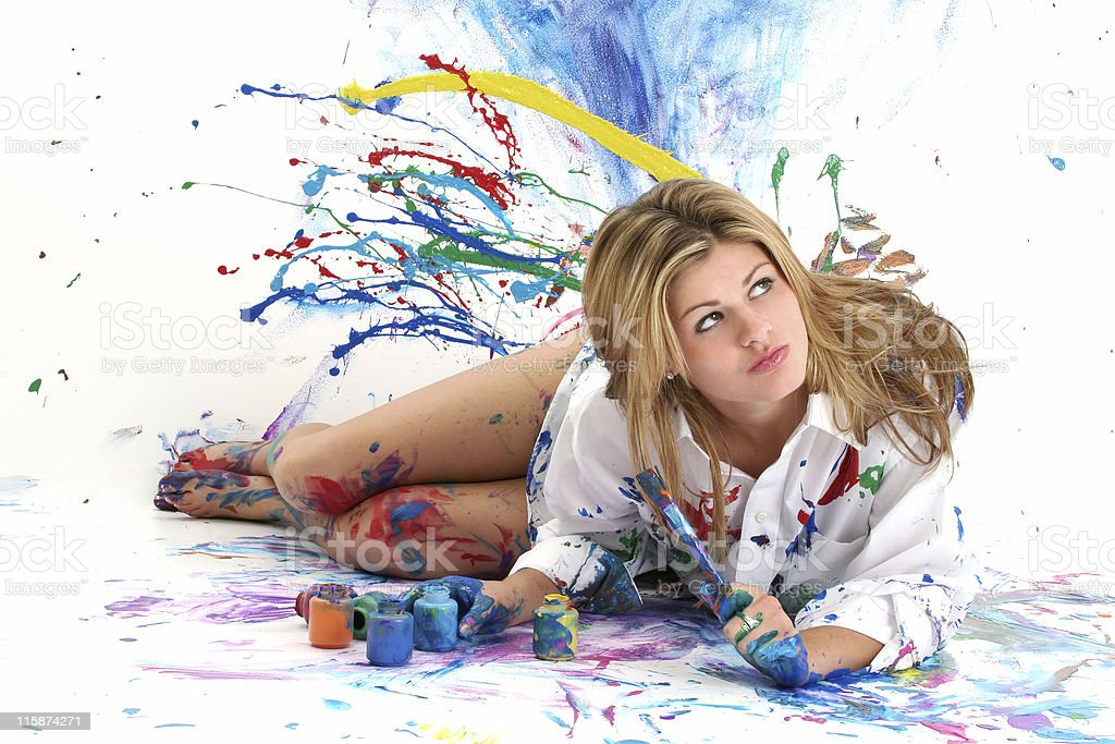 Beautiful young woman painting in a white room stock photo