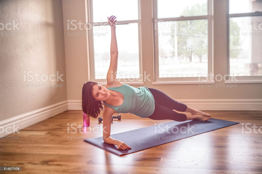 Beautiful Young Woman Performing Perfect Side Plank in Yoga stock photo