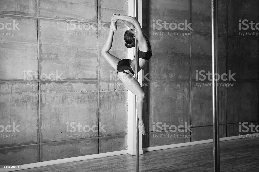 Beautiful young woman performing pole dance elements stock photo