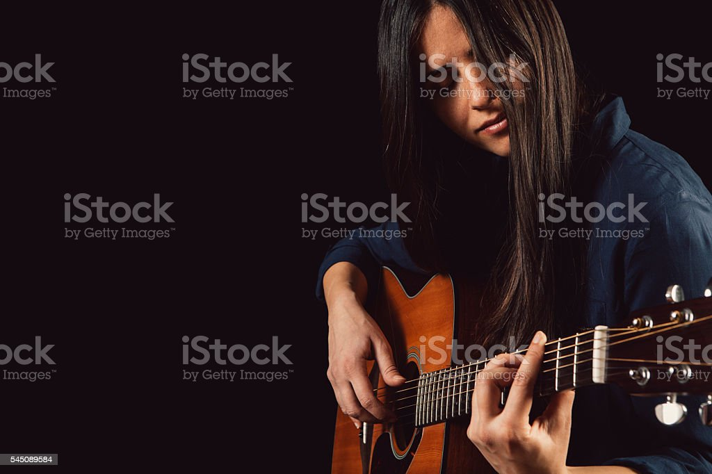 beautiful young woman playing acoustic guitar stock photo