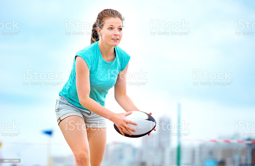 Beautiful young woman playing beach rugby in Summer stock photo