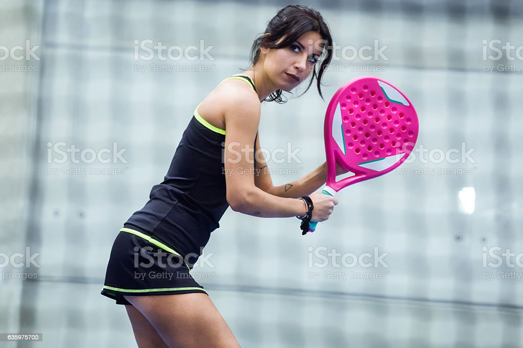 Beautiful young woman playing paddle tennis indoor. stock photo
