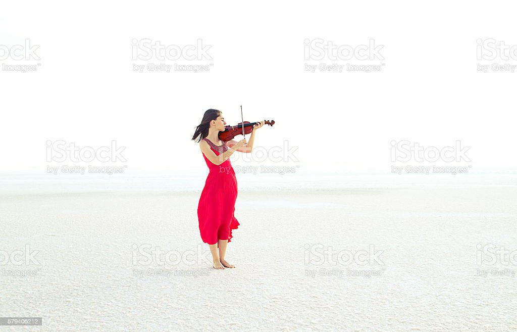 Beautiful young woman playing violin on snow stock photo