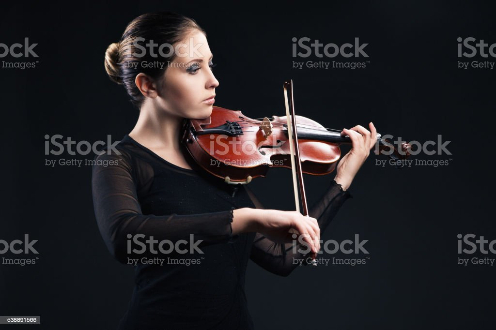 Beautiful young woman playing violin over black stock photo