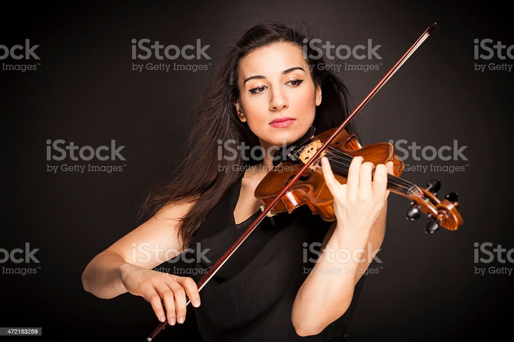 Beautiful young woman playing violin stock photo