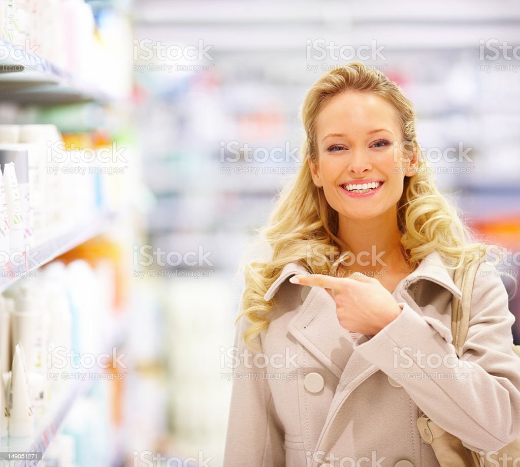 Beautiful young woman pointing at beauty products in mall stock photo