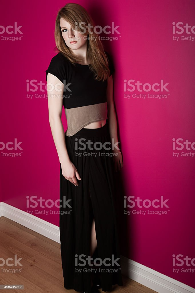 Beautiful young woman posing against pink wall stock photo