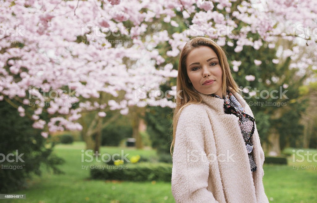Beautiful young woman posing at spring garden stock photo