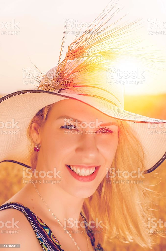 Beautiful young woman posing in the field. Filter used stock photo