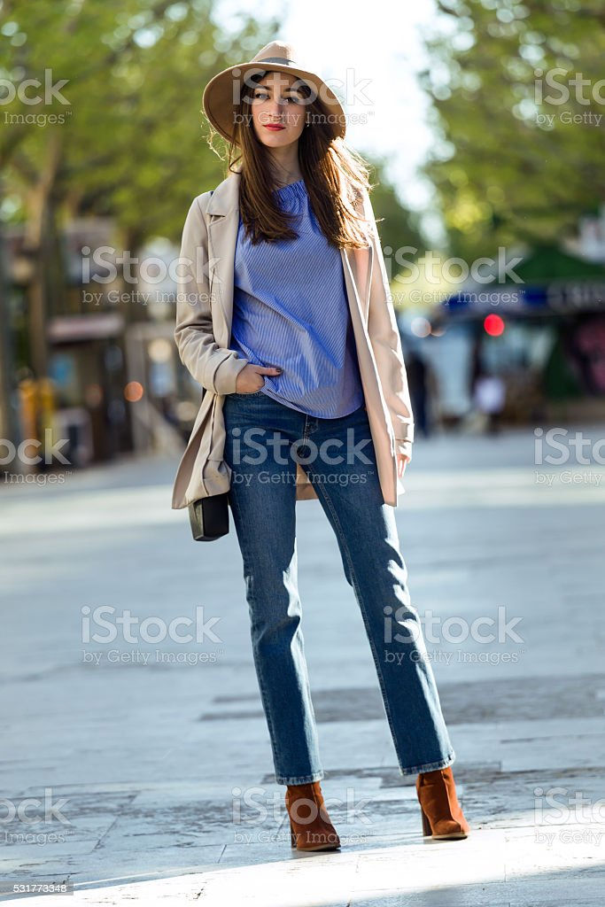 Beautiful young woman posing in the street. stock photo