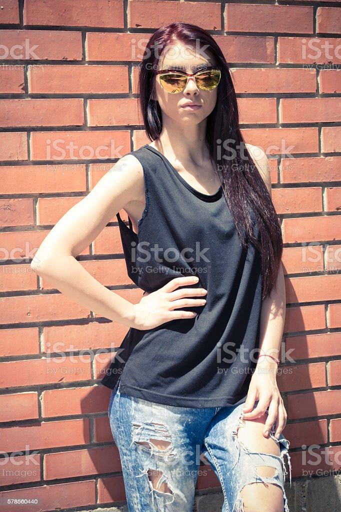 Beautiful young woman posing next to the brick wall stock photo
