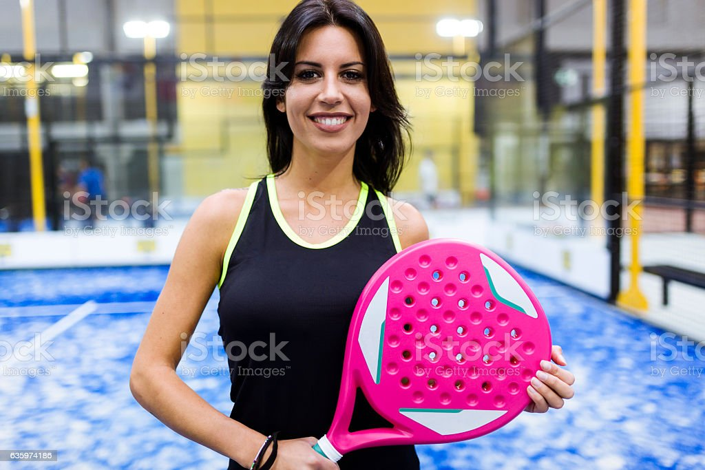 Beautiful young woman posing on paddle tennis court. stock photo