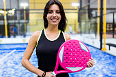 Beautiful young woman posing on paddle tennis court.