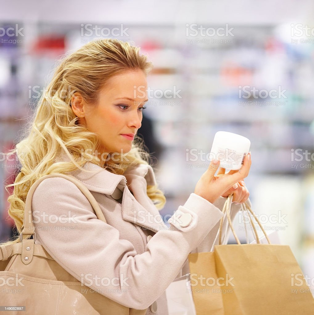 Beautiful young woman purchasing a beauty product in mall royalty-free stock photo