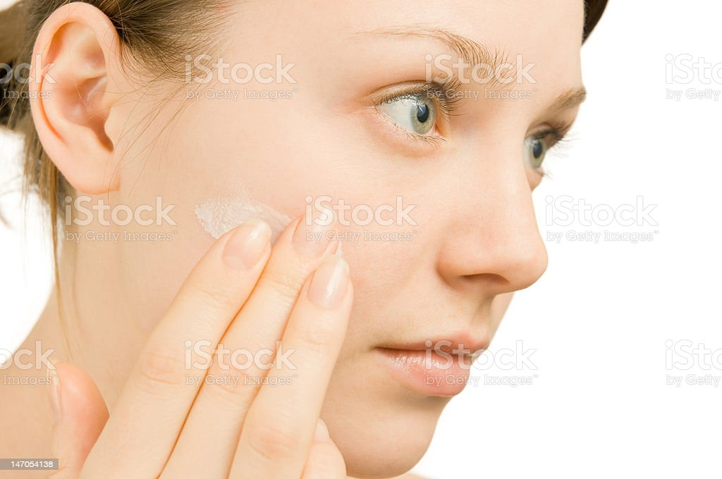 Beautiful young woman putting cream on her face royalty-free stock photo