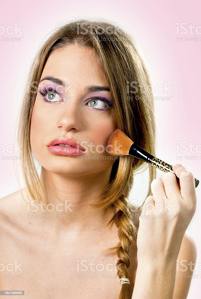 Beautiful young woman putting on makeup,pink background , serious royalty-free stock photo