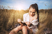 beautiful young woman reading a book on a meadow