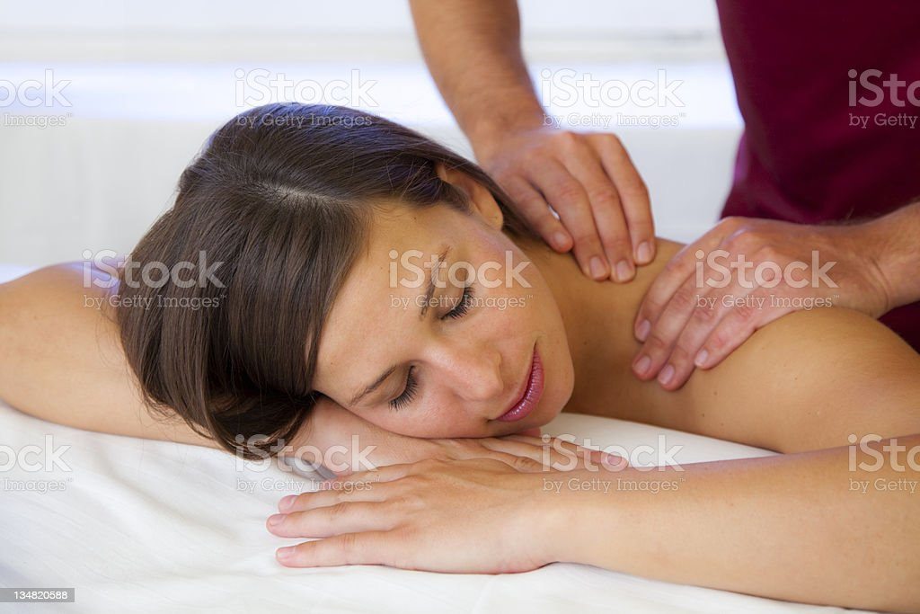 Beautiful young woman receives massage on her shoulder stock photo