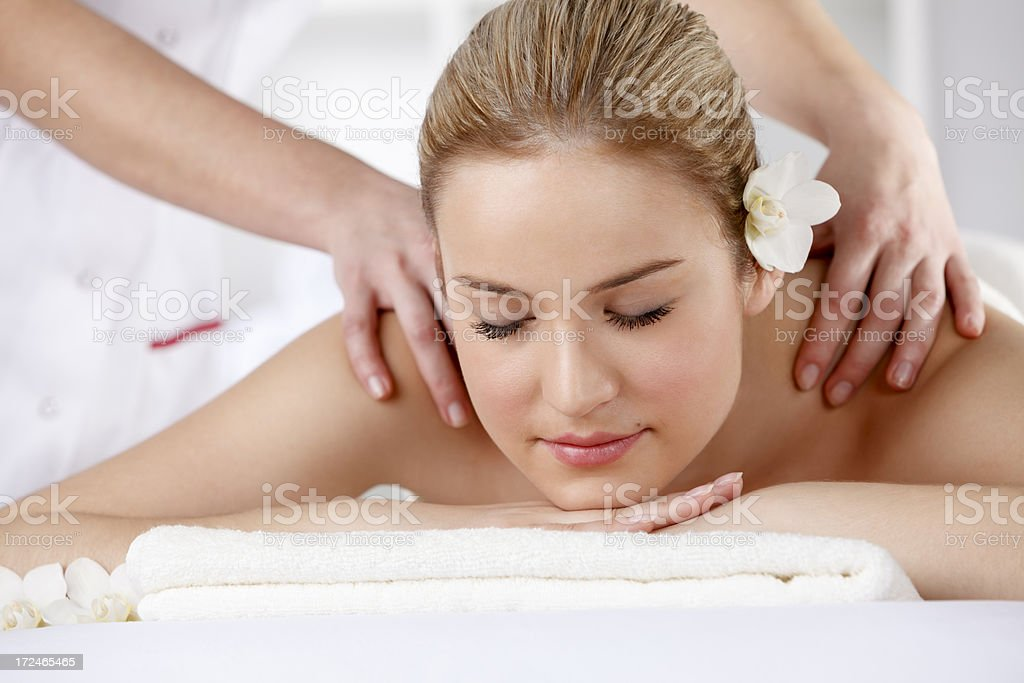 Beautiful young woman receiving back massage at spa stock photo
