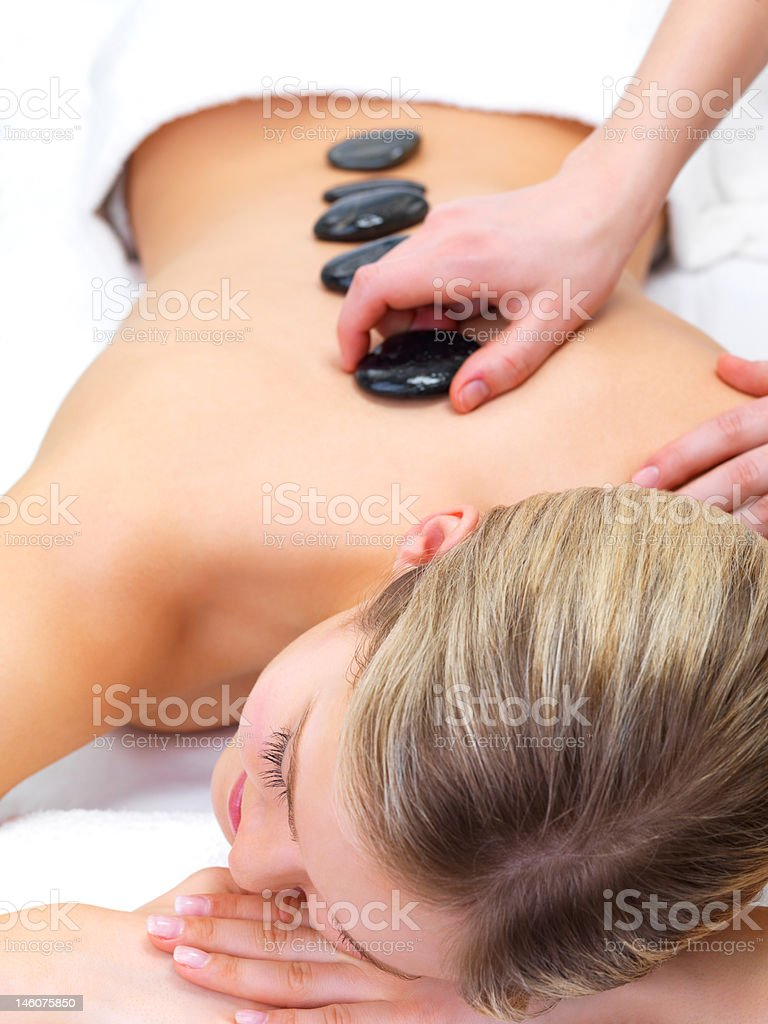 Beautiful young woman receiving hot stone massage at day spa royalty-free stock photo