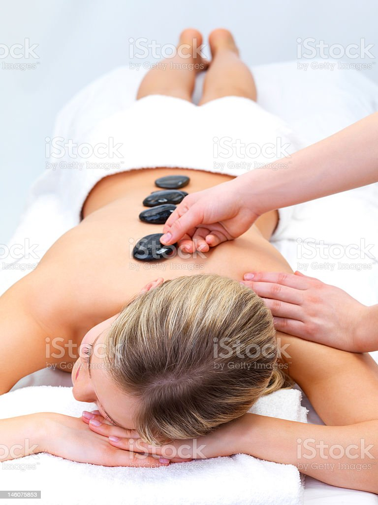 Beautiful young woman receiving hot stones massage at day spa royalty-free stock photo